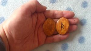 Naud-runan är nedvänd och As-runan synlig och rättstående.